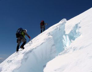 Mountain climbers ascending a steep, snow-covered slope.