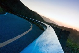 Close-up of a guardrail on a winding road at twilight.
