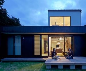 Two people on the patio of a modern home at twilight