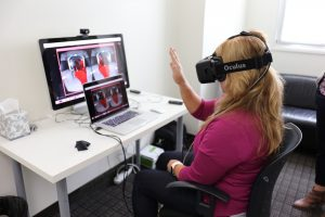 Woman wearing VR Headset interacts with a virtual user interface.